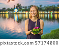 A female tourist holds the Loy Krathong in her hands and is about to launch it into the water. Loy 57174800