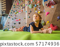 Boy resting after climbing a rock wall indoor 57174936