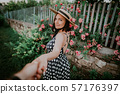 Elegant woman in retro dress and hat holding hand of her man on roses background 57176397