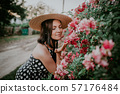 Elegant young woman in retro styled dress and hat posing on roses background. 57176484
