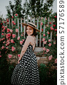 Elegant young woman in retro styled dress and hat posing on roses background.  57176589