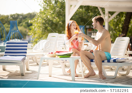 Couple drinking cold cocktail while chilling near pool 57182291