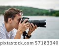 Man taking photos with a telephoto lens 57183340