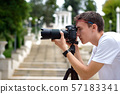 Man taking photos with a telephoto lens 57183341