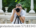 Man taking photos with a telephoto lens 57183343