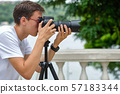 Man taking photos with a telephoto lens 57183344