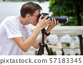 Man taking photos with a telephoto lens 57183345