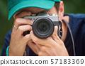 Man taking photos with retro style camera 57183369