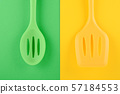 bright kitchen utensils on yellow and green background, creative idea 57184553