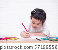 Asian little cute girl sitting and use color pencil drawing cartoon in white paper on wooden table. Learning and education of kid. 57199558
