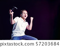 Happy boy with open mouth and joystick shouting for joy after winning in video game on black 57203684