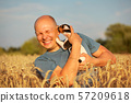 Man in wheat field, afternoon light, holding Jack 57209618