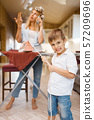 Housewife talking by phone, kid fooling with iron 57209696