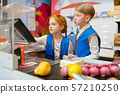 Girl and boy in uniform at the register, sellers 57210250