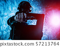 SWAT fighter aiming pistol from behind shield 57213764
