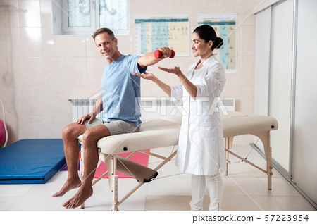 Male patient is doing exercise with dumbbell 57223954
