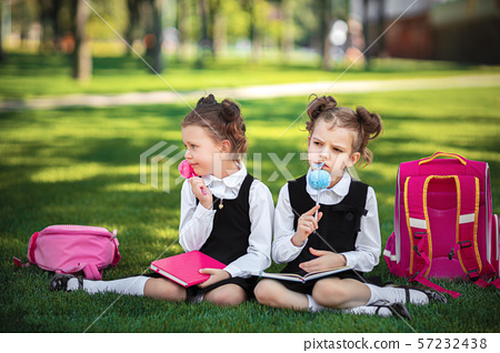 Two Little school girls with pink backpack sitting on grass after lessons and thinking ideas, read 57232438