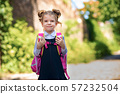 Smiling student girl wearing school backpack. Portrait of happy Caucasian young girl outside the 57232504