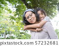Cute Asian mother and daughter playing and  giving ride on back together at park 57232681