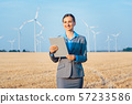 Investor in wind turbines with computer evaluating her investment on site 57233586