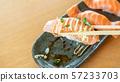 chopsticks tong fresh salmon sushi on a wooden 57233703