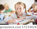 Smiling girl with freckles smiling while writing at the lesson 57234628