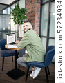 Bearded man sitting in armchair and working on laptop 57234934