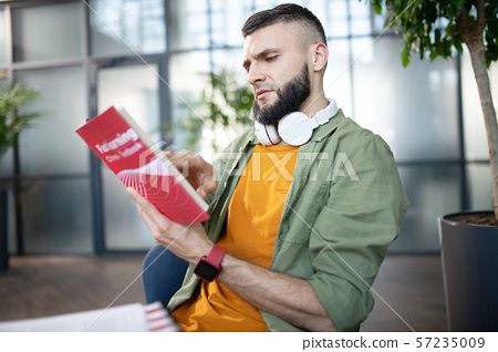 Bearded man with earphones on neck reading book 57235009