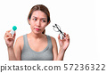 Asian woman holding glasses and contact lens on 57236322
