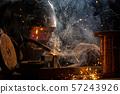 Welder is welding metal part in factory 57243926