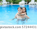Brother and sister play water in swimming pool 57244431
