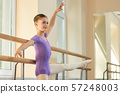 Positive young ballerina doing exercises. 57248003