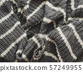 Gray knitted sweater with white stripes. Folded warm clothing. Crumpled textile background. 57249955