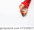 Woman is holding New Year decoration - red heart on white background. Top view on decoration for Christmas tree. 57249957