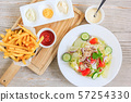 french fries and ketchup on a wooden plate and Salad with fresh vegetables and tuna 57254330