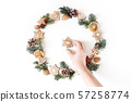 Christmas circle floral composition with womans hand holding cookie. Wreath of fir tree branches 57258774
