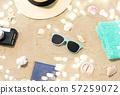 camera, passport, sunglasses and hat on beach sand 57259072