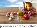 glasses and bottles of apple juice on wooden table 57259645