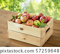 ripe apples in wooden box on table 57259648