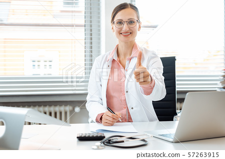 Doctor woman giving thumbs-up sitting on desk in her office 57263915