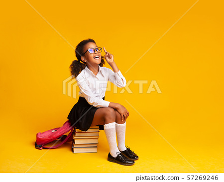 Cute Afro Schoolgirl Pointing Finger Up Sitting On Book Stack 57269246