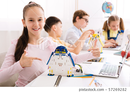 Girl showing her robot, pointing finger on it 57269282