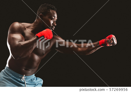 Side view of black fighter making punch over black background 57269956
