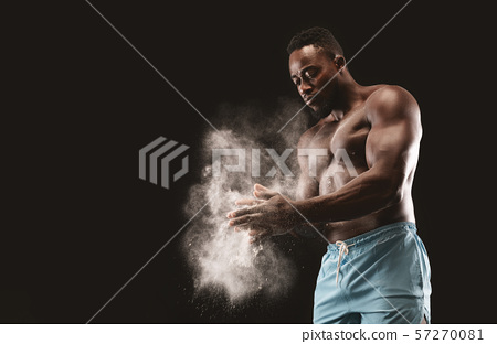 Young bare-chested black sportsman applying talcum powder on his hands 57270081