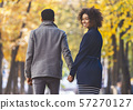 Back view of walking afro couple over autumn park 57270127