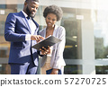 Couple of african american business partners working while standing outdoors 57270725