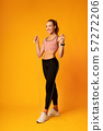 Girl Doing Jump Rope Workout Over Yellow Background 57272206