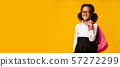 Smiling Black Elementary Student Girl Holding Backpack, Yellow Background, Panorama 57272299