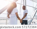Cheerful african man and woman holding hands at airport 57272364