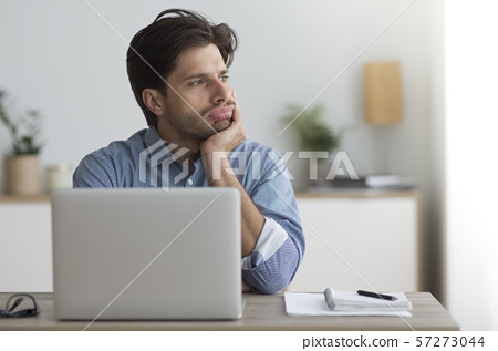 Bored Guy Sitting At Laptop Computer In Office 57273044